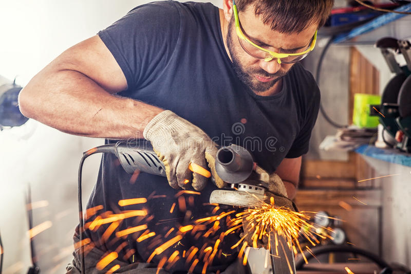 Man processes metal an angle grinder. A young man welder in a black T-shirt, goggles and construction gloves processes metal an angle grinder in the garage, in royalty free stock photography