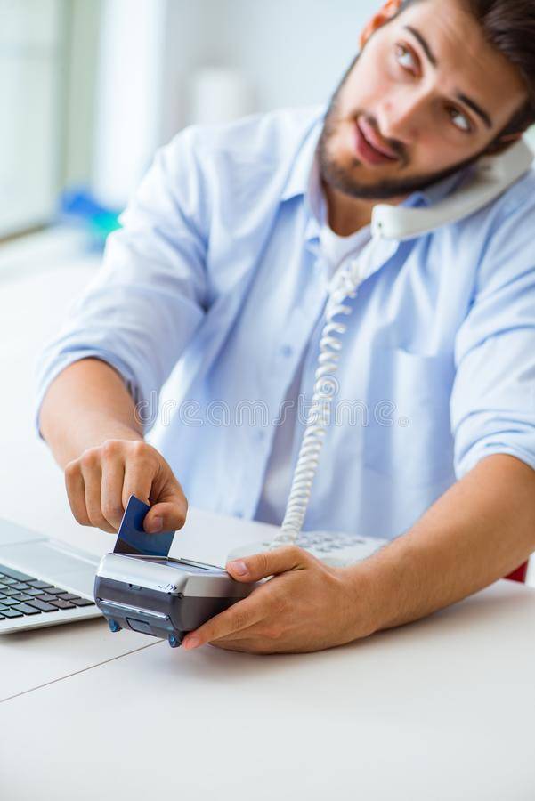 The man processing credit card transaction with pos terminal. Man processing credit card transaction with POS terminal stock images