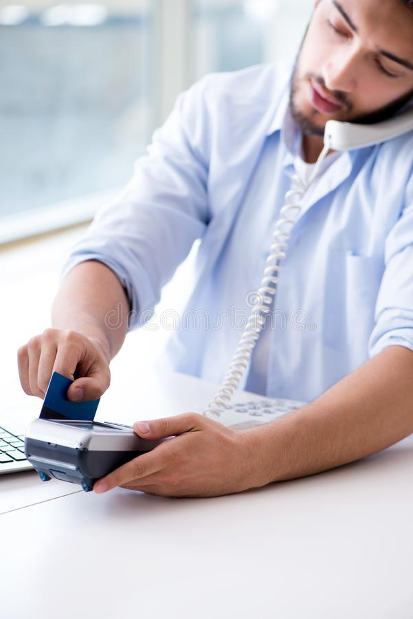 The man processing credit card transaction with pos terminal. Man processing credit card transaction with POS terminal royalty free stock images