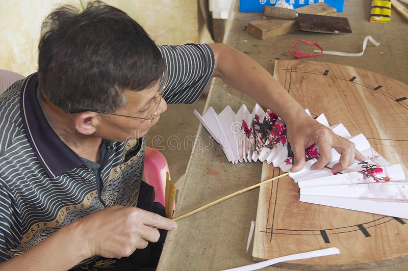 Man produces traditional Chinese fan in Yangshuo, China. stock image