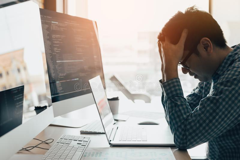 Man programmers are stressed and hand holding head with headache at the office while working analyzing on desk in code at office royalty free stock photo