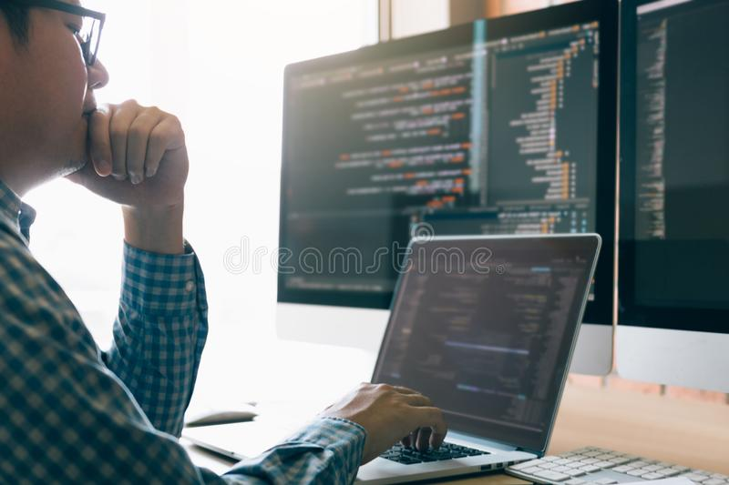 Man programmers are stressed and hand holding nose with headache at the office while working analyzing on desk in code at office. Room stock image