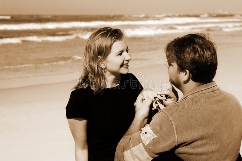 Man proposing. Young man proposing marriage to his girlfriend on the beach. High contrast sepia image royalty free stock image