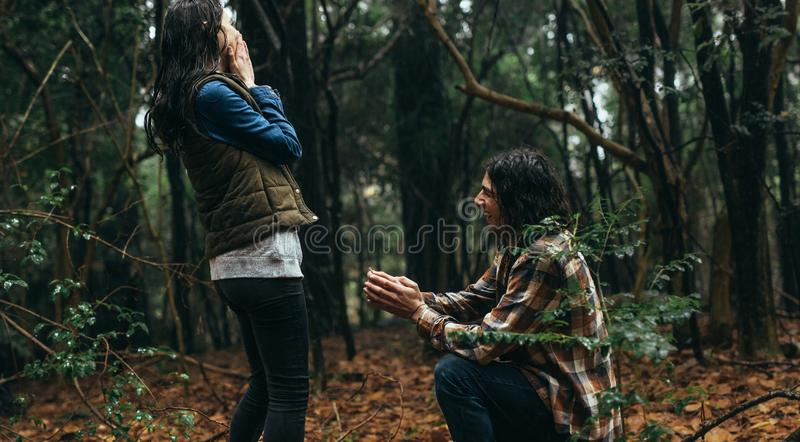 Man proposing his girlfriend at forest. Couple in forest, with men proposing his girlfriend. Man kneeling holding a ring and making a marriage proposal to women stock photos