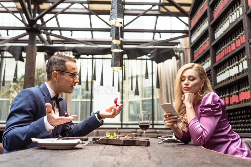Man proposing his girlfriend while she using smartphone with bored expression. At restaurant royalty free stock photography