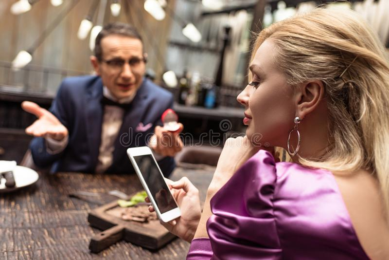 Man proposing his girlfriend while she using smartphone. At restaurant stock photo