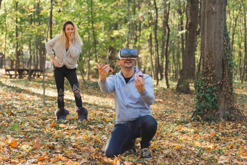 Man proposing his virtual girl and real girl is shocked. Love concept. Man proposing his virtual girl and real girl is shocked stock image