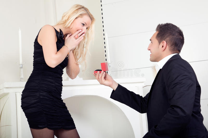 Man proposing marriage. Handsome young men down on bended knee proposing marriage to a beautiful blond women who is completely overwhelmed with surprise and joy stock photo