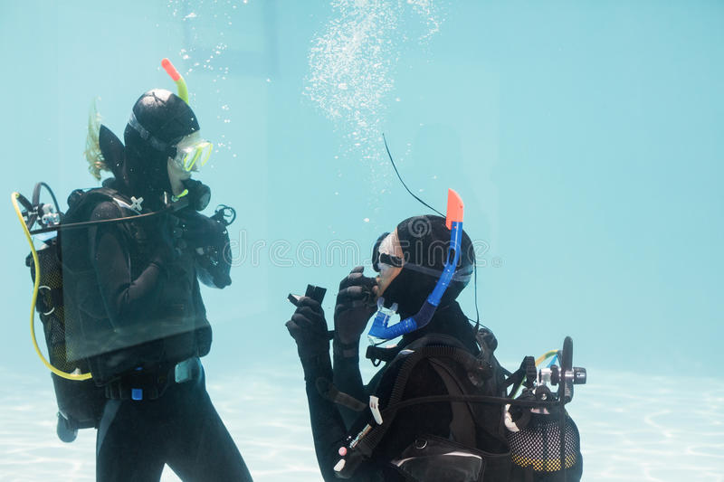 Man proposing marriage in scuba gear. Man proposing marriage to the shocked women underwater in scuba gear stock images