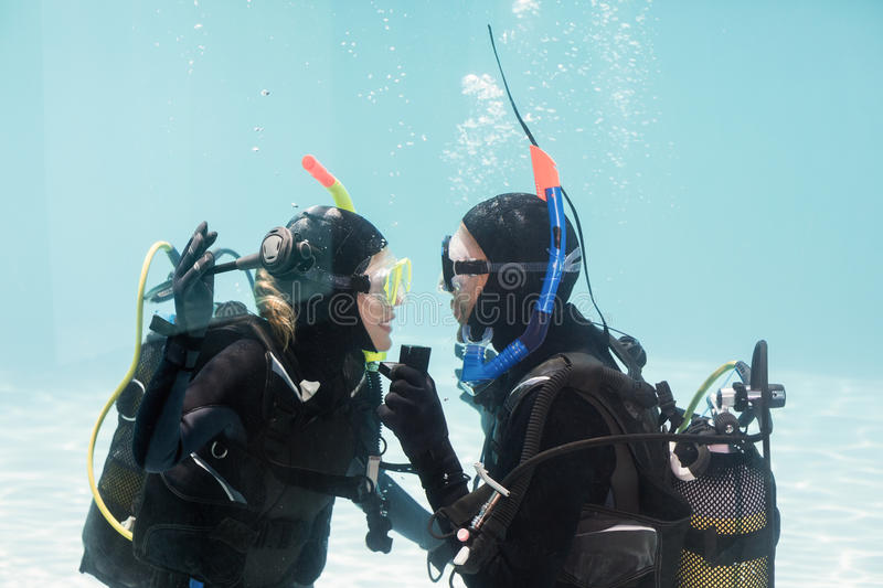 Man proposing marriage in scuba gear. Man proposing marriage to the shocked women underwater in scuba gear royalty free stock photography