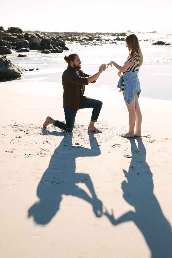 Man proposing marriage to his girlfriend on the beach stock photography