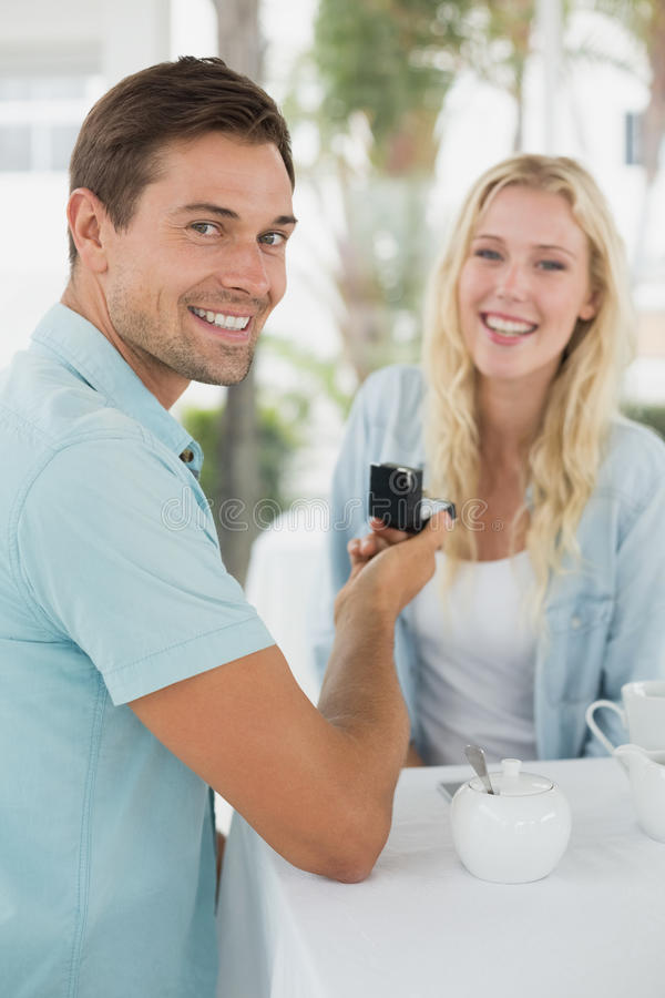 Man proposing marriage to his shocked blonde girlfriend. On the cafe terrace on sunny day royalty free stock photos