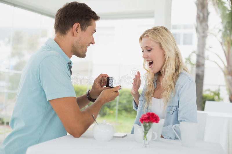 Man proposing marriage to his shocked blonde girlfriend. On the cafe terrace on sunny day royalty free stock images