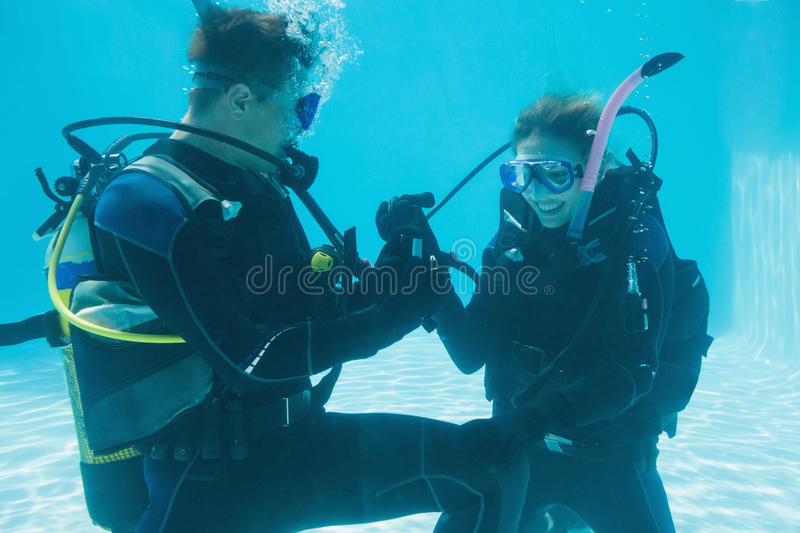 Man proposing marriage to his shocked girlfriend underwater in scuba gear. On their holidays stock image