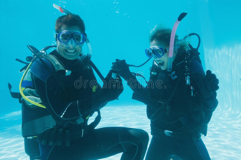 Man proposing marriage to his shocked girlfriend underwater in scuba gear. On their holidays royalty free stock photos