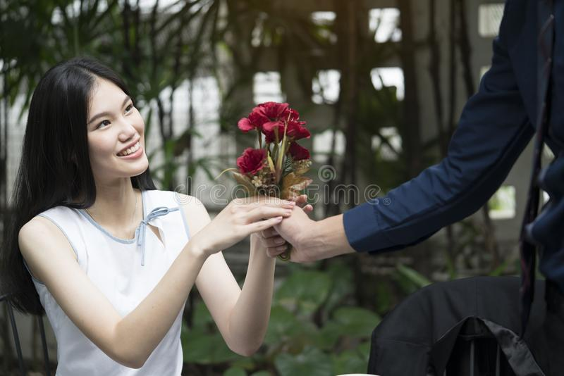 A man is proposing marriage to a smiling woman. With a lovely flower bouquet in a beautiful garden, lover and couple concept, surprising proposal royalty free stock photos