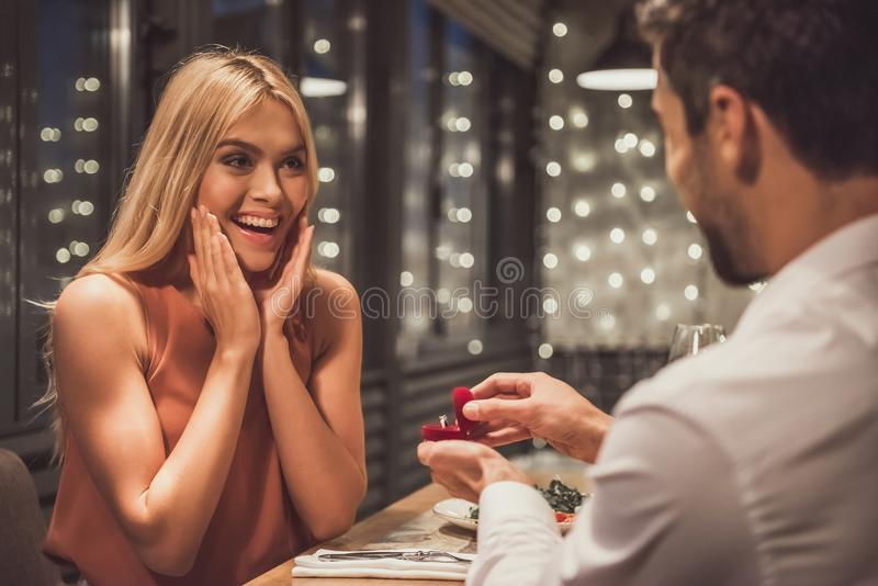 Man proposing in restaurant. Beautiful young women is smiling while her boyfriend is holding an engagement ring and proposing to her in a restaurant royalty free stock photos