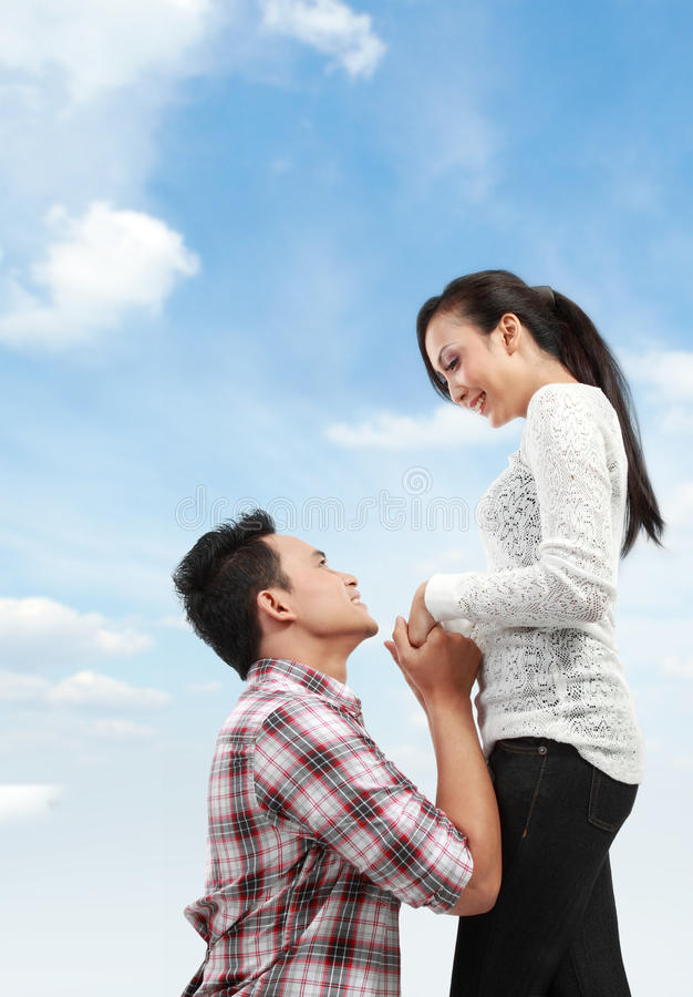 Man proposing to girlfriend. Young men romantically proposing to girlfriend under the blue sky royalty free stock images