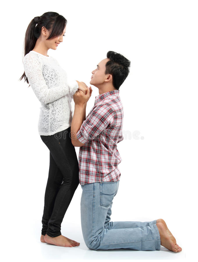 Man proposing to girlfriend. Young men romantically proposing to girlfriend isolated on white background stock images