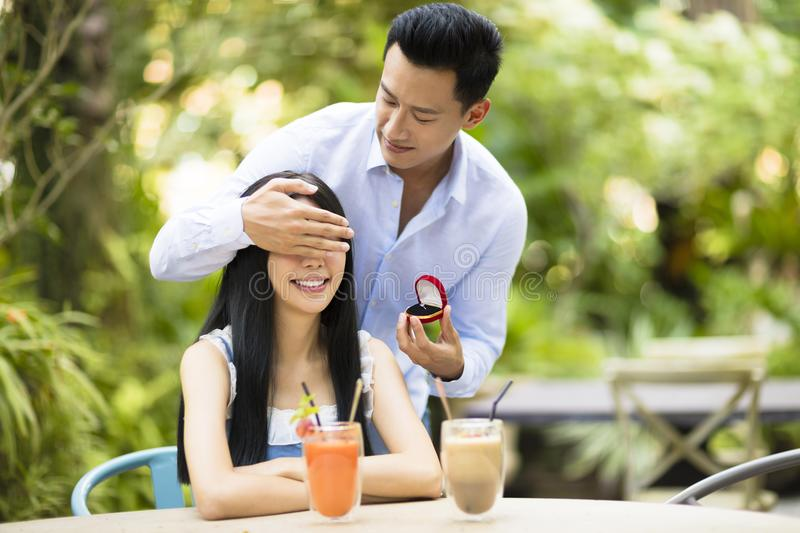 Man proposing to girlfriend offering engagement ring. In restaurant royalty free stock image
