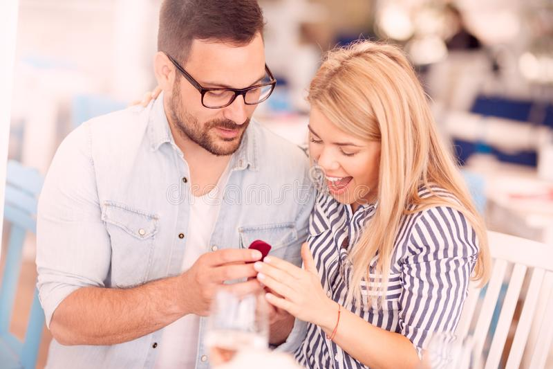 Man proposing to girlfriend in restaurant. Surprised girl looks into the ring, love, emotion, anniversary royalty free stock photo