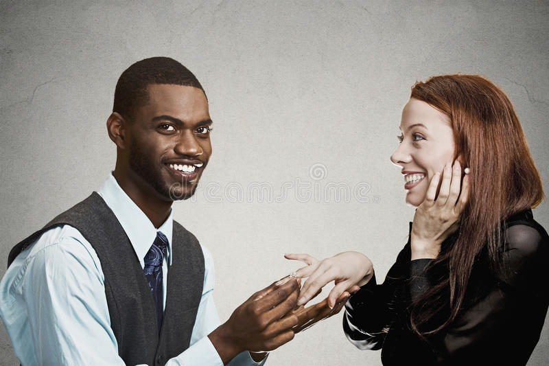 Man proposing to happy, excited woman. Closeup portrait couple, handsome happy men proposing to excited smiling young women grey black background. Holidays, love stock photography