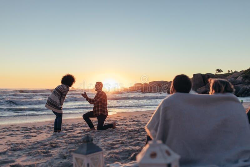 Man proposing to his girlfriend at sea shore royalty free stock photos