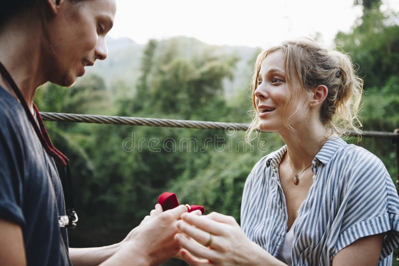 Man proposing to his happy girlfriend outdoors love and marriage concept royalty free stock images