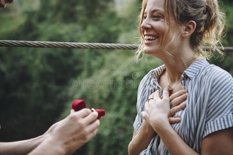 Man proposing to his woman with an engagement ring in the red box stock photo