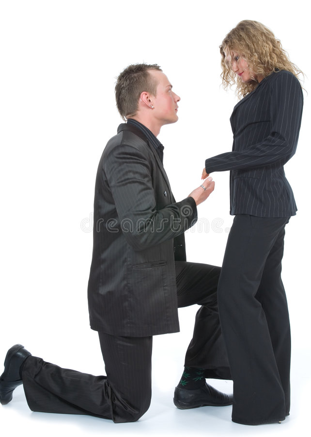 Man proposing to woman. Man kneeling in front of woman; looks as if he is proposing marriage royalty free stock image
