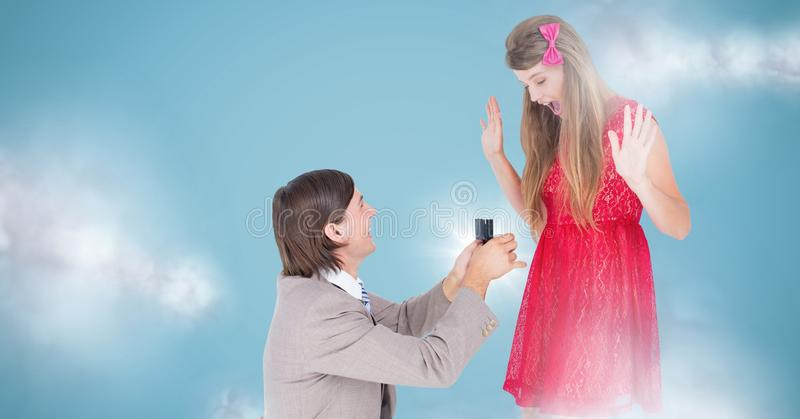 Man proposing to woman against blue background with clouds. Digital composite of Man proposing to women against blue background with clouds royalty free stock photography