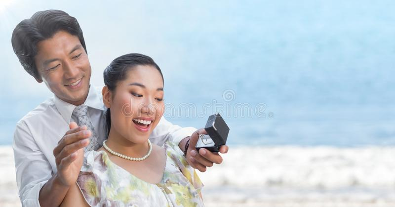 Man proposing to woman against blurry beach. Digital composite of Man proposing to women against blurry beach royalty free stock photography