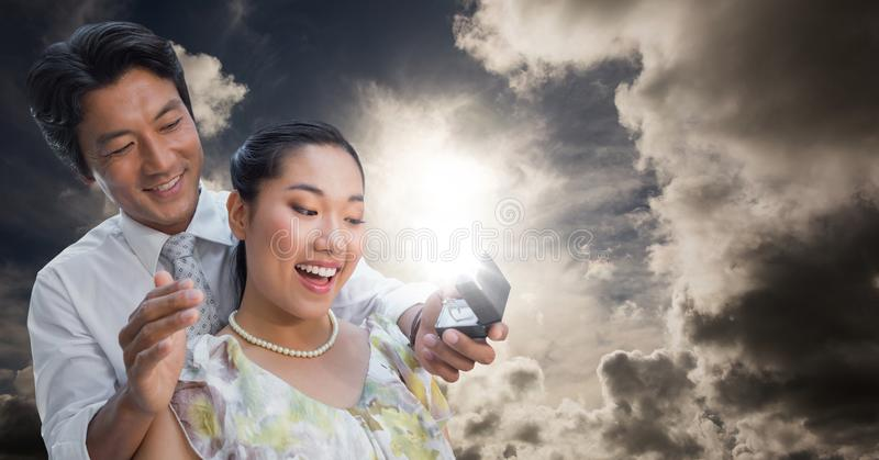 Man proposing to woman against sky. Digital composite of Man proposing to women against sky royalty free stock photo