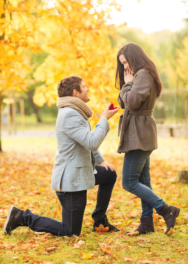 Man proposing to a woman in the autumn park. Holidays, love, couple, relationship and dating concept - kneeled men proposing to a women in the autumn park royalty free stock photography