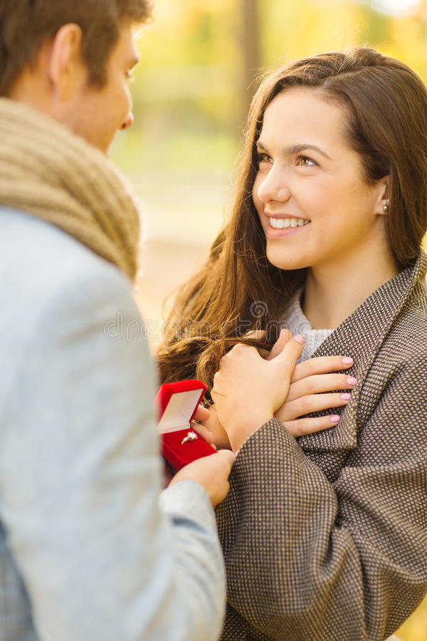 Man proposing to a woman in the autumn park stock photos