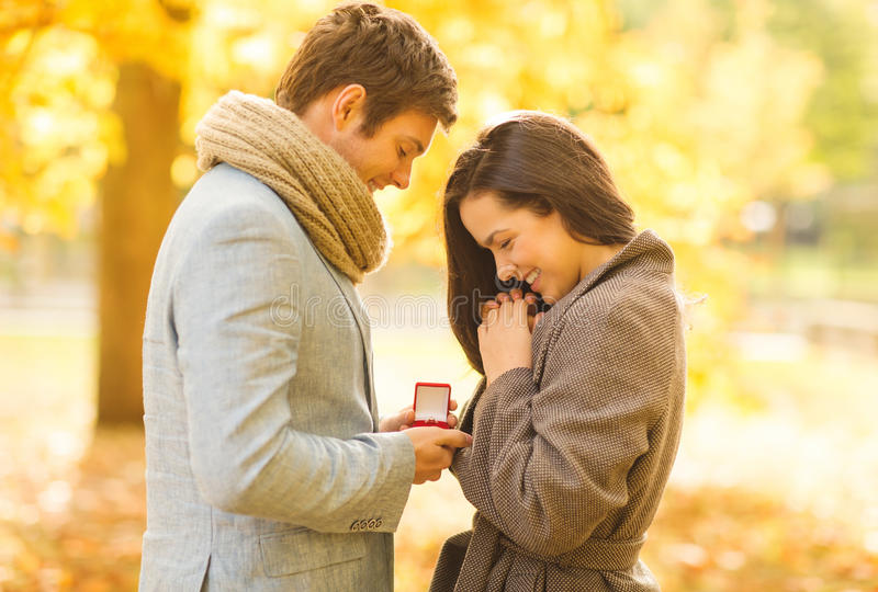 Man proposing to a woman in the autumn park. Holidays, love, couple, relationship and dating concept - romantic men proposing to a women in the autumn park royalty free stock photo