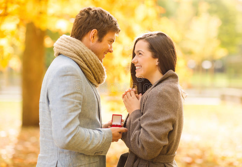 Man proposing to a woman in the autumn park. Holidays, love, couple, relationship and dating concept - romantic men proposing to a women in the autumn park stock image