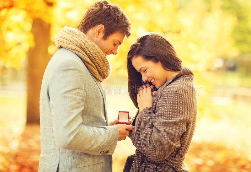 Man proposing to a woman in the autumn park. Holidays, love, couple, relationship and dating concept - romantic men proposing to a women in the autumn park royalty free stock photos