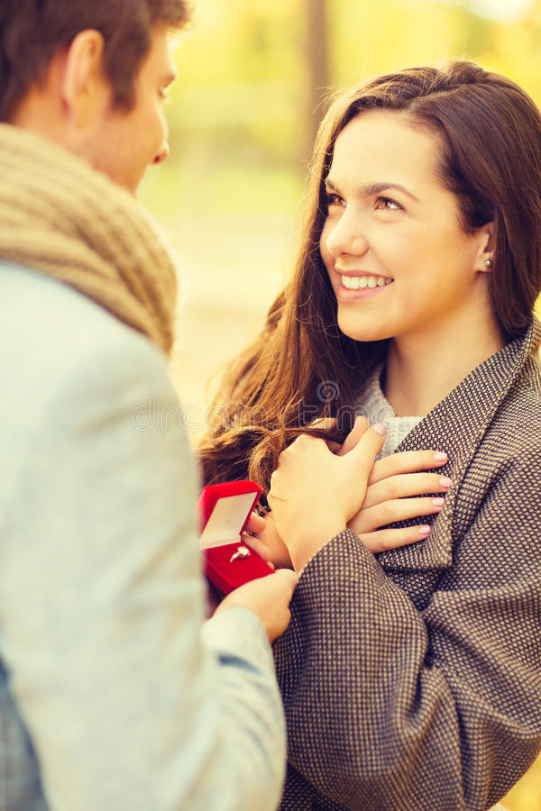 Man proposing to a woman in the autumn park. Holidays, love, couple, relationship and dating concept - romantic men proposing to a women in the autumn park stock photo