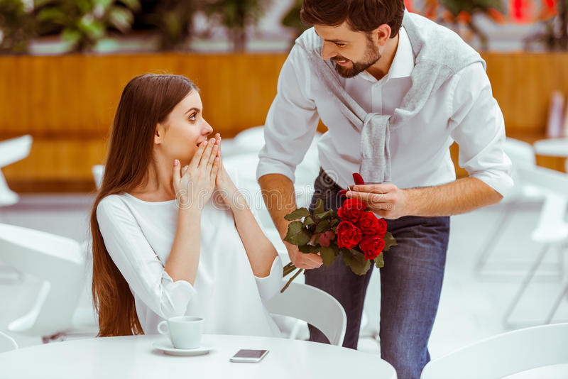 Man proposing to woman. Handsome men with bunch of red roses and wedding ring proposing to his beautiful women in cafe stock image