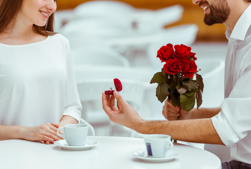 Man proposing to woman. Handsome men with bunch of red roses and wedding ring proposing to his beautiful women in cafe, cropped stock photo
