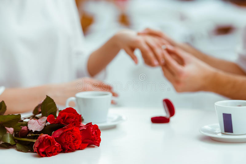 Man proposing to woman. Handsome men putting wedding ring on and proposing to his beautiful women in cafe. Bunch of red roses on a table, close-up royalty free stock image