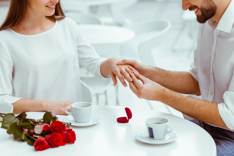 Man proposing to woman. Handsome men putting wedding ring on and proposing to his beautiful women in cafe. Bunch of red roses on a table, cropped stock image
