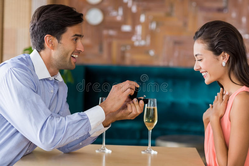 Man proposing to woman offering engagement ring. Man proposing to women offering engagement ring in restaurant stock image