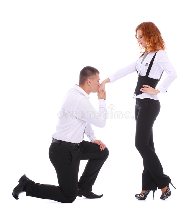 Man proposing to woman while standing on one knee. Young men proposing to a women while standing on one knee and kissing her hand on white background royalty free stock photos
