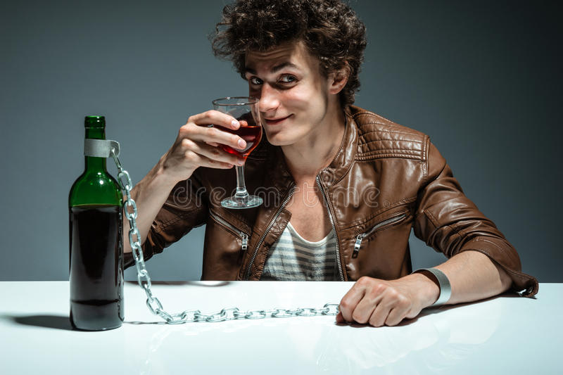 Man proposing a toast with a glass of red wine and looking at the camera. Photo of youth addicted to alcohol, alcoholism concept, social problem stock photos
