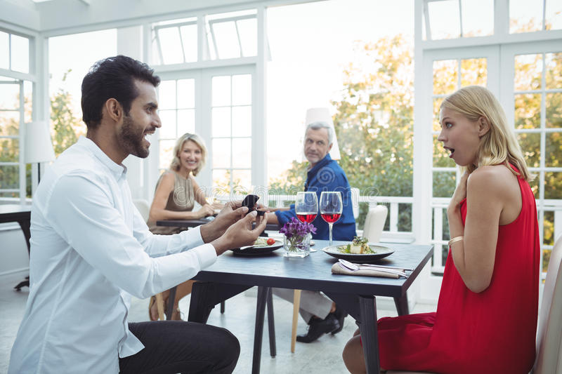 Man proposing woman while having meal. In restaurant stock images