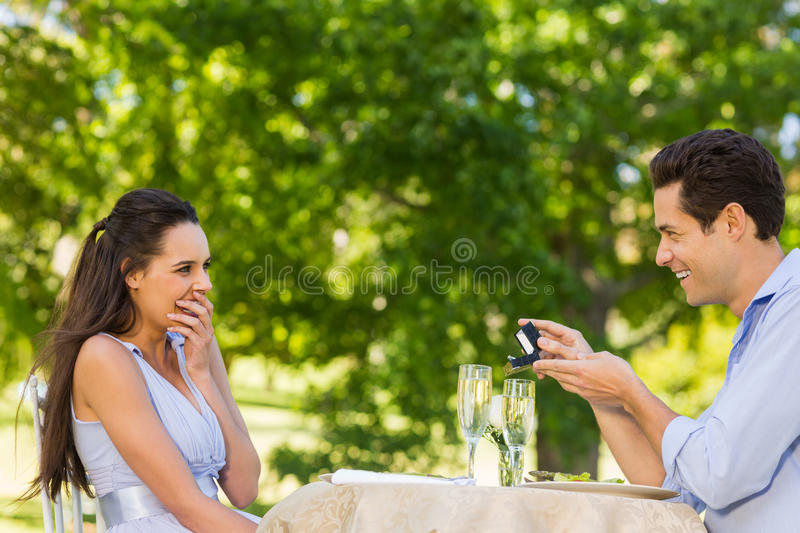 Man proposing woman at an outdoor café. Side view of a men proposing women while they have a romantic date at an outdoor caf stock photo