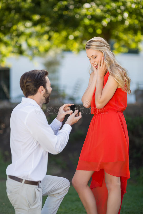 Man proposing a woman with a ring on his knee. In the park stock images