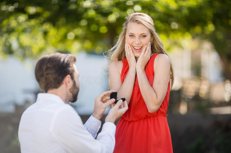 Man proposing a woman with a ring on his knee. In the park royalty free stock image